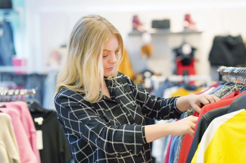 Young girl chooses things in a clothing store stock photography