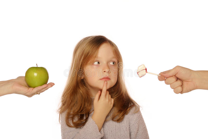 Young girl choosing between an apple and candy royalty free stock photos