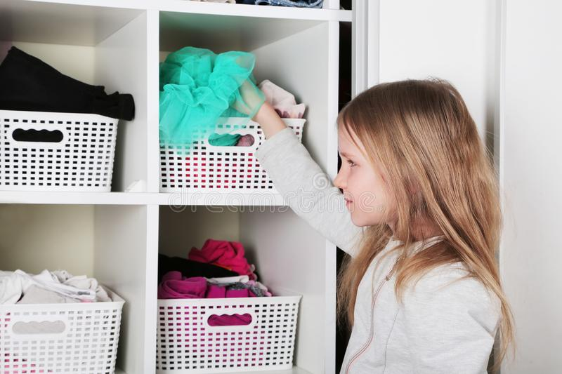 Young girl choosing dress in wardrobe at home. The wardrobe which put in order. All things are folded neatly. Many boxes. Everythi. Ng is in its place. Harmony stock photos