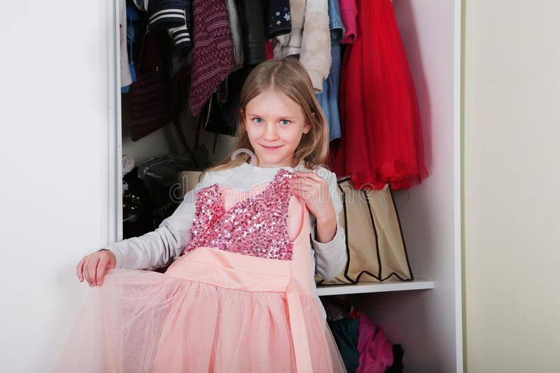 Young girl choosing dress in wardrobe at home. The wardrobe which put in order. All things are folded neatly. Many boxes. Everythi. Ng is in its place. Harmony stock photography