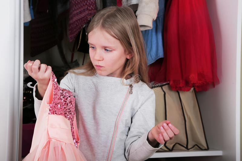 Young girl choosing dress in wardrobe at home. The wardrobe which put in order. All things are folded neatly. Many boxes. Everythi. Ng is in its place. Harmony royalty free stock photography
