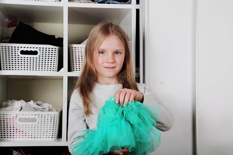 Young girl choosing dress in wardrobe at home. The wardrobe which put in order. All things are folded neatly. Many boxes. Everythi. Ng is in its place. Harmony royalty free stock image