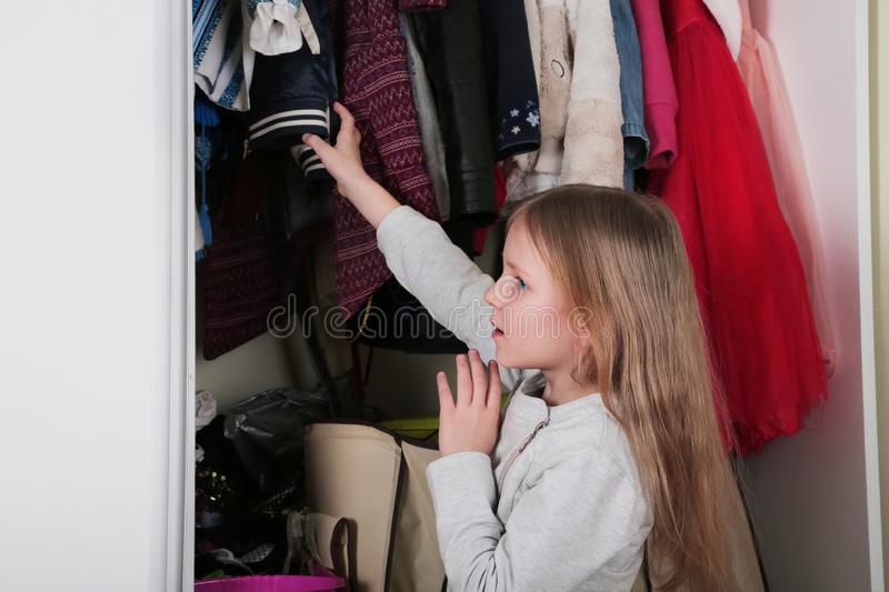 Young girl choosing dress in wardrobe at home. The wardrobe which put in order. All things are folded neatly. Many boxes. Everythi. Ng is in its place. Harmony stock photo