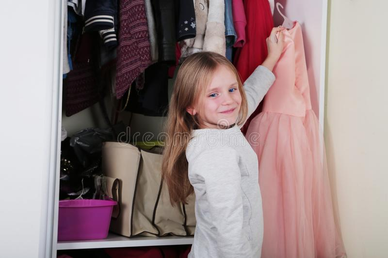 Young girl choosing dress in wardrobe at home. The wardrobe which put in order. All things are folded neatly. Many boxes. Everythi. Ng is in its place. Harmony royalty free stock images