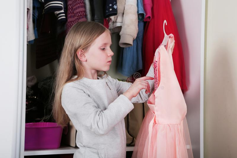 Young girl choosing dress in wardrobe at home. The wardrobe which put in order. All things are folded neatly. Many boxes. Everythi. Ng is in its place. Harmony royalty free stock photos