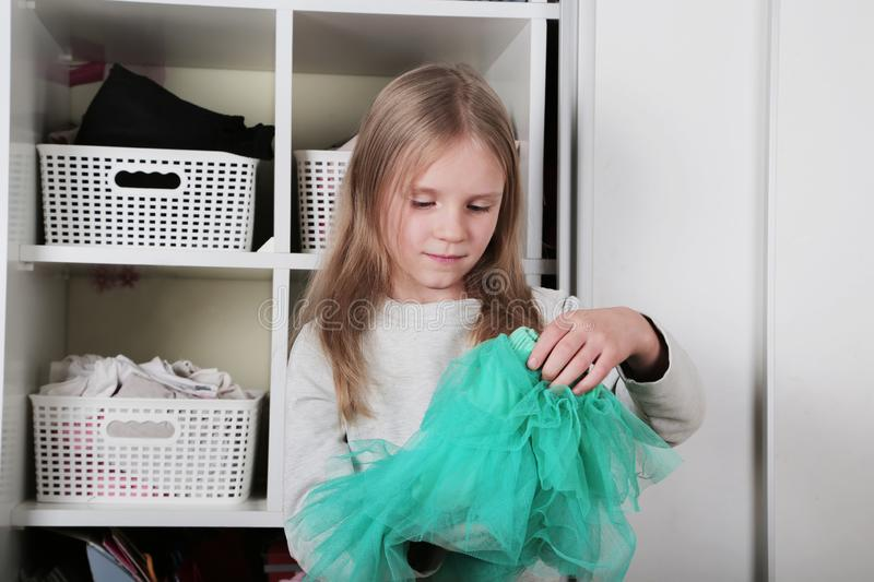 Young girl choosing dress in wardrobe at home. The wardrobe which put in order. All things are folded neatly. Many boxes. Everythi. Ng is in its place. Harmony stock images