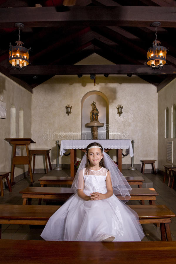 Young girl in church wearing first communion dress stock photos