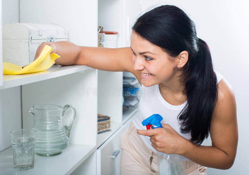 Young girl cleaning in house. Beautiful young girl in white undershirt does cleaning in house royalty free stock image