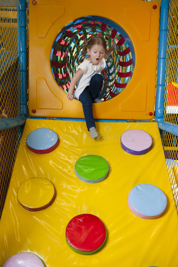 Young girl climbing down ramp in soft play centre stock images