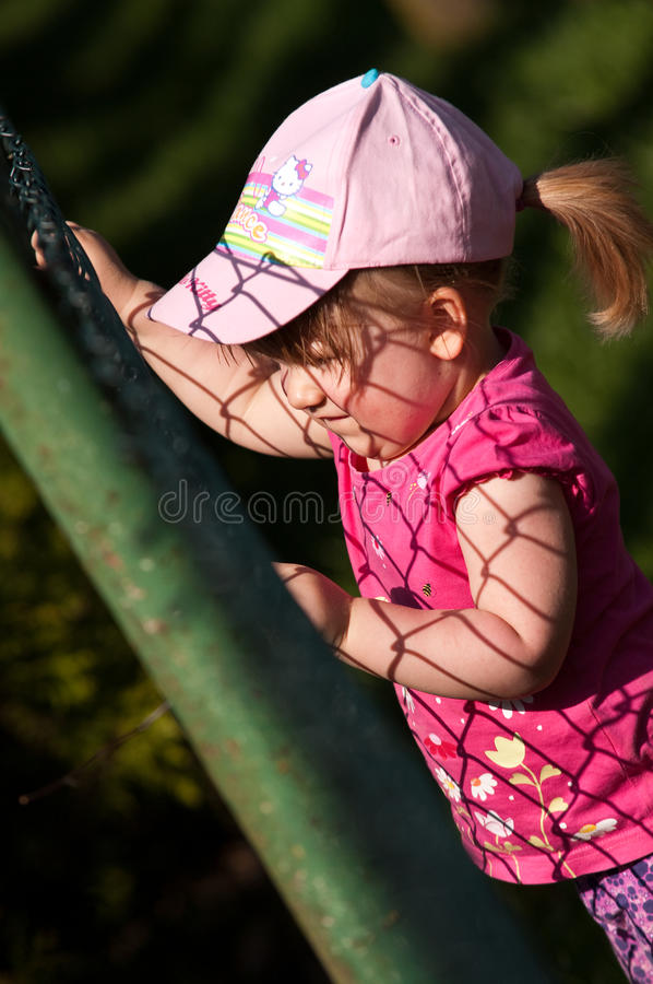 Download Young Girl Climbing On Fence Stock Image - Image: 24741543