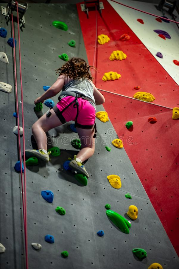 Young girl climbing up on practice wall in indoor rock gym. View of Young girl climbing up on practice wall in indoor rock gym royalty free stock photo
