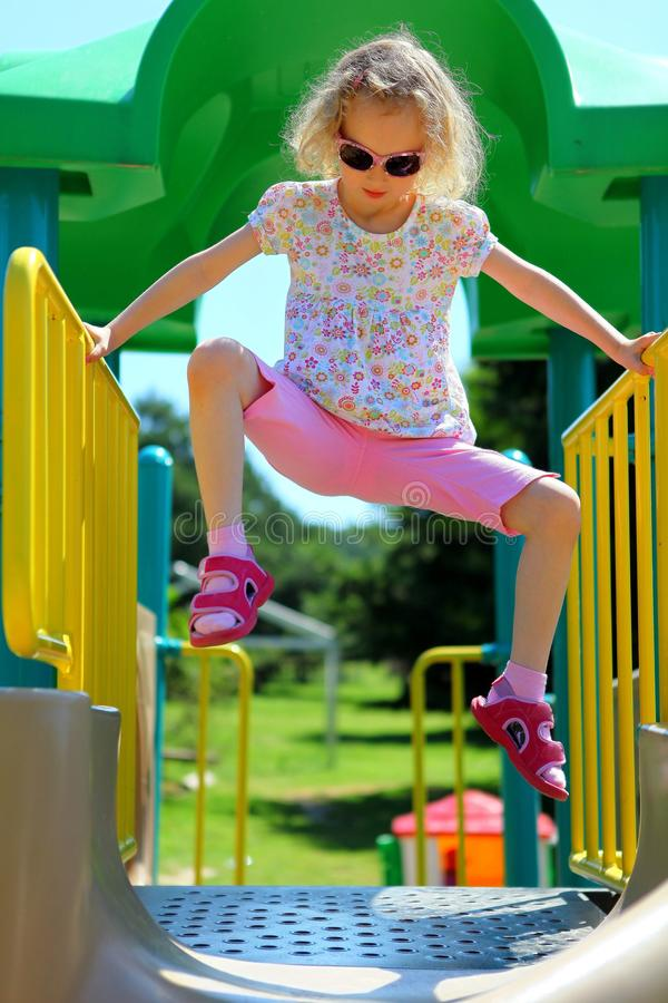 Young girl climbing on yellow handrail - Holding on hands only stock images