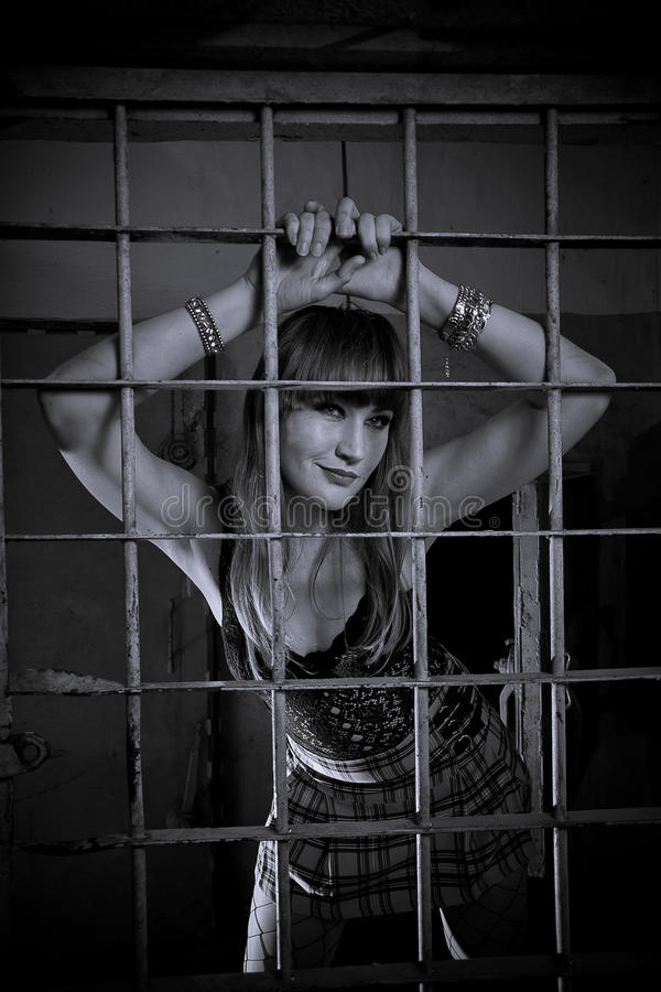 Young girl closed behind bars, grid, like in prison. looking in short skirt stock photos