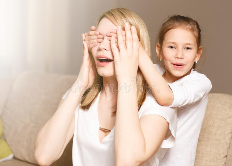 Young girl is closing her mother eyes. Beautiful mother and her little daughter are smiling. People happiness, leisure royalty free stock photos