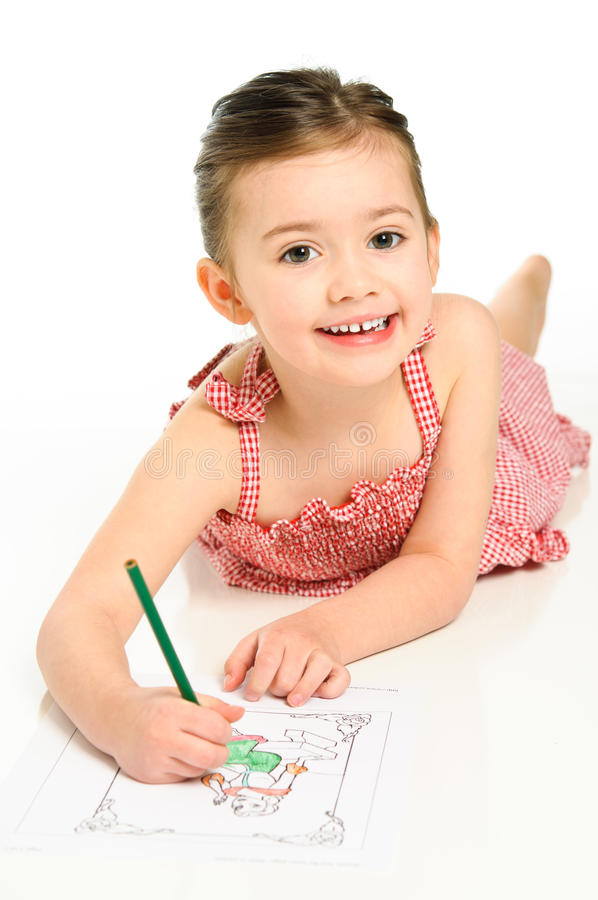 Young Girl Coloring. Young preschool aged girl coloring a picture in a red checkered dress stock image