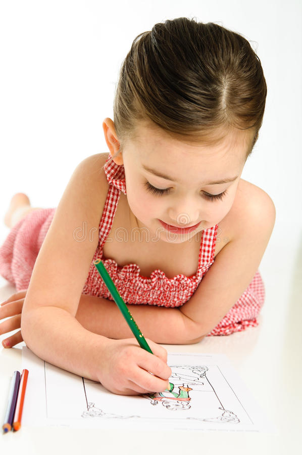 Young Girl Coloring. Young preschooler girl coloring a picture in a red checkered dress stock photography
