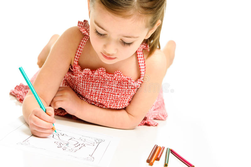 Young Girl Coloring with Pencils. Young preschooler girl coloring a picture in a red checkered dress stock photo