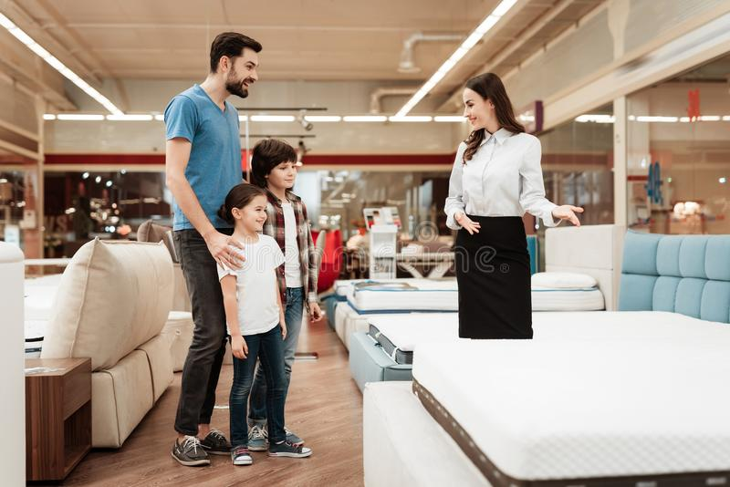 Young girl consultant demonstrates orthopedic mattress to young father with children in furniture store. Purchase of orthopedic mattress. Sale of orthopedic stock images