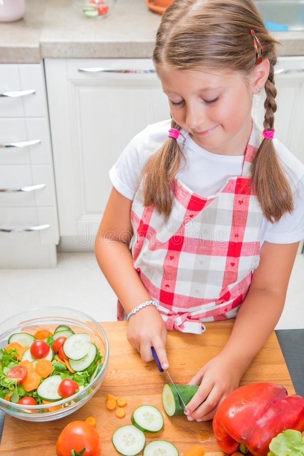 young girl is cooking salad at home stock images