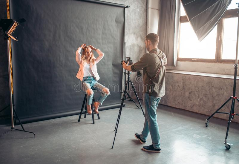 Young girl in cool jeans with holes sitting with raised arms stock photo