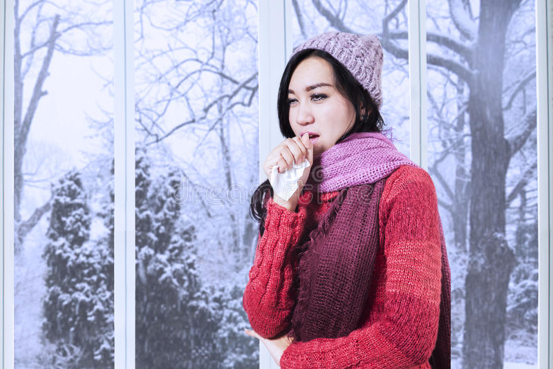 Young girl coughing at tissue. Portrait of lovely girl wearing a warm clothes and coughing at tissue at home stock photo