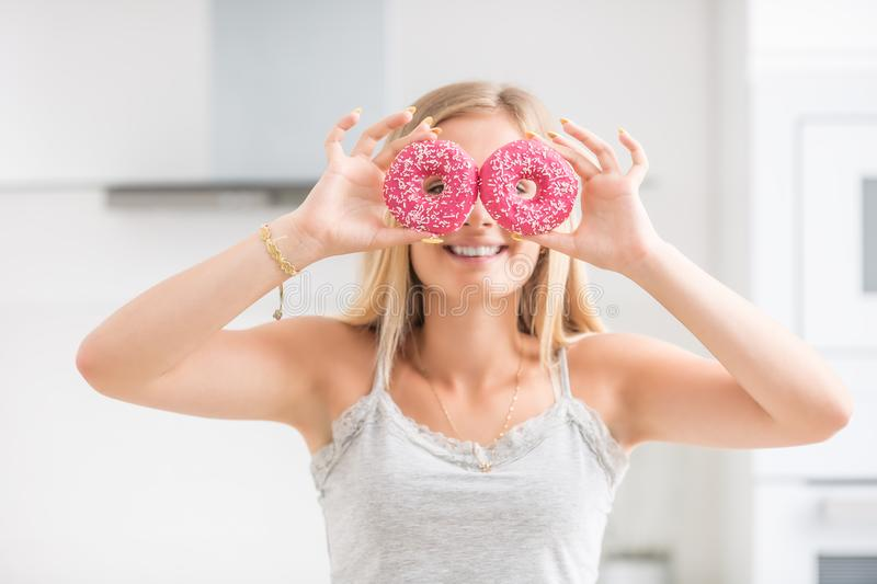Young girl covered her face with pink donuts in home kitchen. Emotion morning at breakfast. Woman, dinner, beautiful, diet, weight, failed, food, healthy, care royalty free stock photo