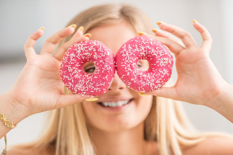 Young girl covered her face with pink donuts in home kitchen. Emotion morning at breakfast royalty free stock photo