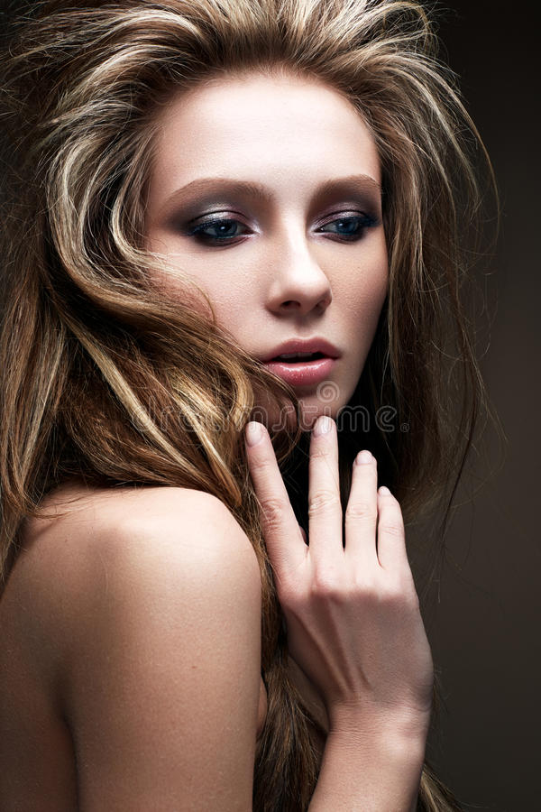 A young girl with a creative bright make-up and a lush hairdo. Beautiful model with smokies. Beauty of the face. Photo is taken in the studio stock photos