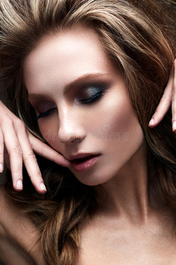 A young girl with a creative bright make-up and a lush hairdo. Beautiful model with smokies. Beauty of the face. Photo is taken in the studio royalty free stock images