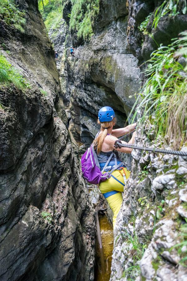 Young girl crossing a via ferrata section on a route called Postalmklamm, in Postalm gorge, Salzkammergut Mountains, near Salzburg royalty free stock images