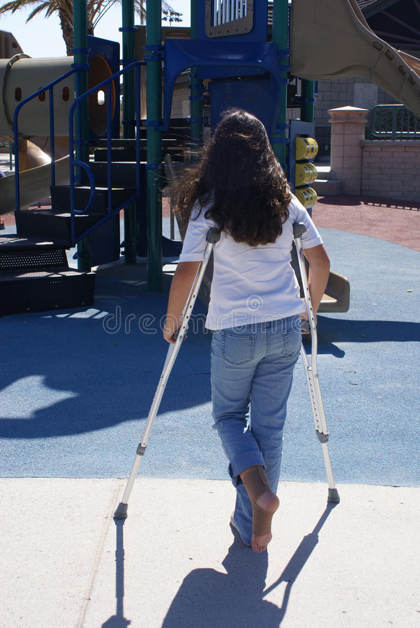 Young Girl with Crutches at Playground stock images