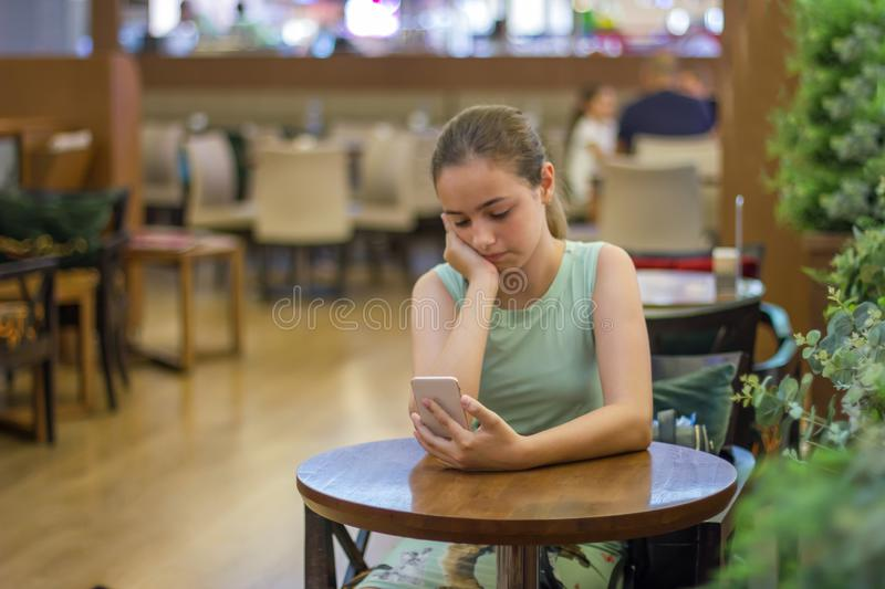 Young girl is crying along in a cafe closing her face with her hand. Teenager broke up with boyfriend stock photos