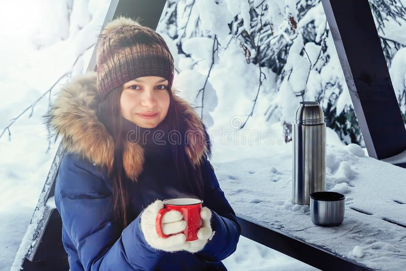 Young girl with a cup of hot coffee in her hands on a bench in the winter snow-covered forest stock photos