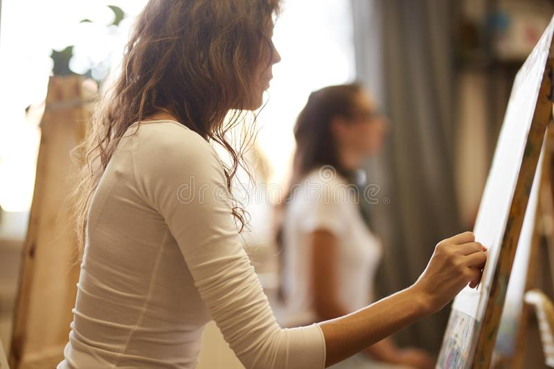 Young girl with curly brown hair dressed in white blouse draws a picture with a pencil in the drawing school royalty free stock photography