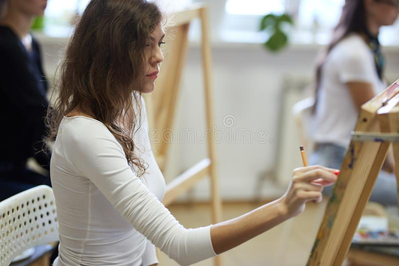 Young girl with curly brown hair dressed in white blouse draws a picture with a pencil in the drawing school.  royalty free stock photography