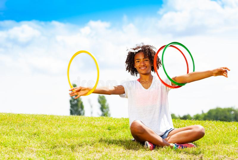 Young girl with curly hair rotate hoops in hands. Young girl with curly hair sit on the lawn in park and rotate hoops on her hands stock photography