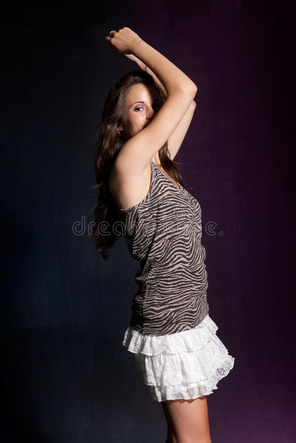 Young girl dancing at disco. Blue and purple stock photography