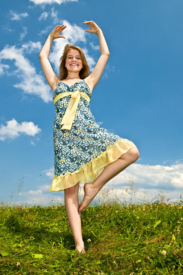 Young girl dancing in meadow stock photo
