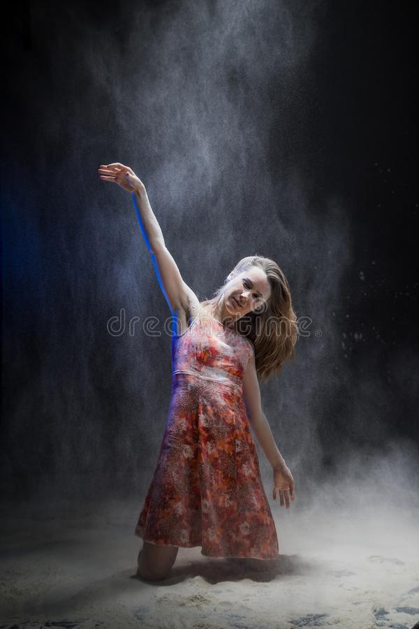 Young girl dancing during photoshoot with flour royalty free stock images