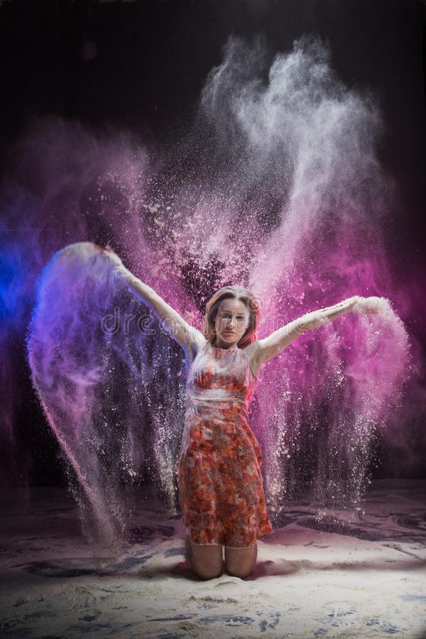 Young girl dancing during photoshoot with flour stock photo