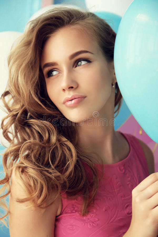 Young girl with dark curly hair and tender makeup, posing with colorful air balloons royalty free stock photos