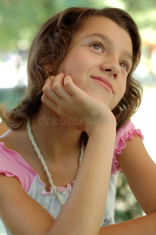 Young girl day dreaming. A young girl sitting and day dreaming stock photos
