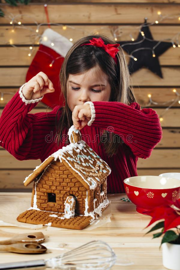Young girl decorating gingerbread house stock image