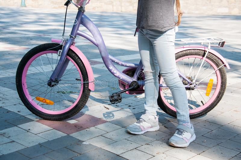 Young girl in denim pants stands near the bike holding it. Summer in the park stock image