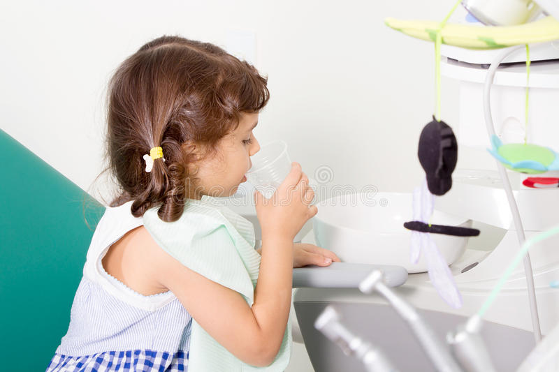 Young girl at dental clinic. Young girl rinses her teeth at dental clinic stock image