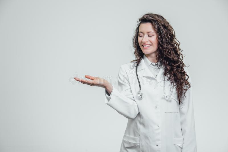 A young girl doctor in a white dressing gown. While pointing it back with the index finger. Showing the product on a stock photo