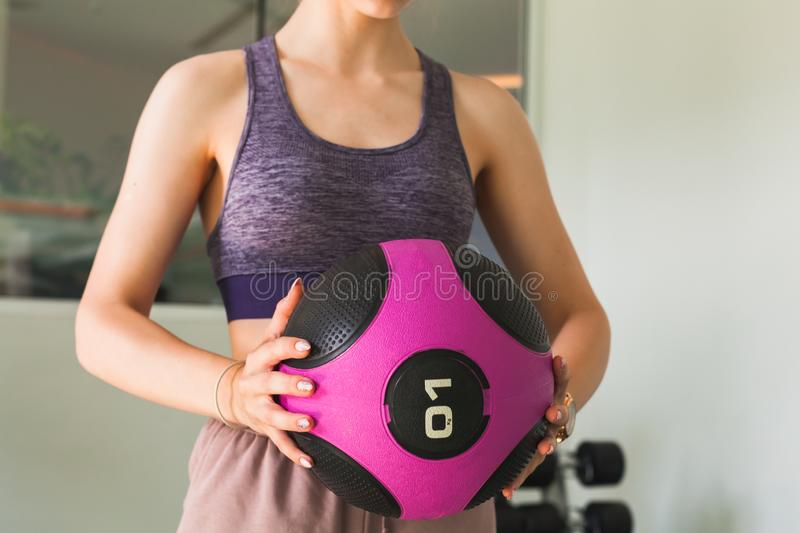 Young girl does an exercise with med ball. Young sporty girl does an exercise with black pink med ball in a gym royalty free stock photography