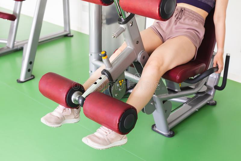Young girl does a leg extension in gym. Young sporty girl does a leg extension exercising in a gym royalty free stock images