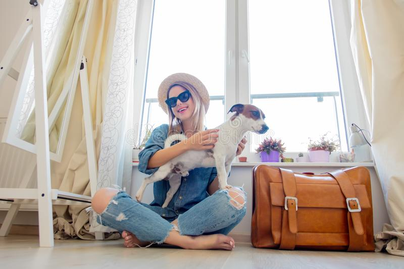 Young girl with dog sitting next to suitcase royalty free stock images