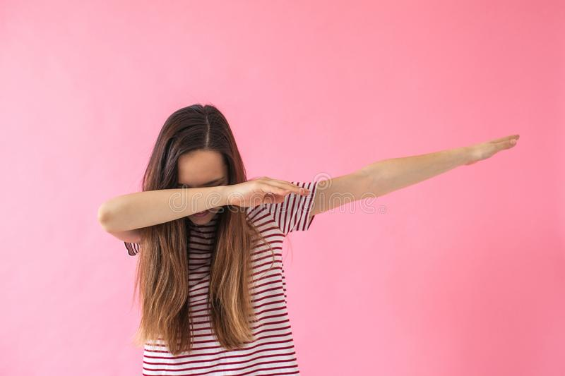 Young girl doing dab dance gesture. Portrait of young brunette girl doing dab dance gesture on pink background. Lifestyle concept royalty free stock photography